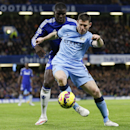 Chelsea's Kurt Zouma, left, vies for the ball with Manchester City's James Milner during the English Premier League soccer match between Chelsea and Manchester City at Stamford Bridge stadium in London, Saturday, Jan. 31, 2015