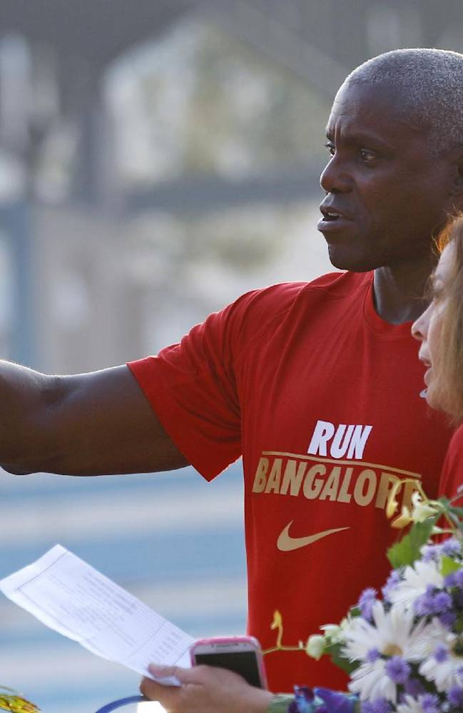 An official watches as U.S. Olympian Carl Lewis, behind,takes a photograph on his mobile phone at the TCS World 10K Bangalore 2014 run in Bangalore, India, Sunday, May 18, 2014. According to organizers, the event had eight races with total prize money of USD 170,000