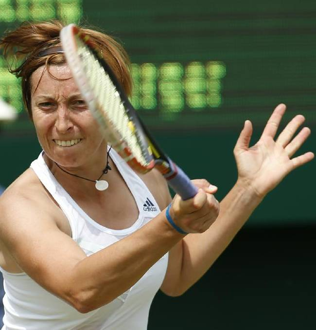 Yvonne Meusburger of Austria plays a return to Vania King of the U.S. during their first round match at the All England Lawn Tennis Championships in Wimbledon, London,  Monday, June  23, 2014