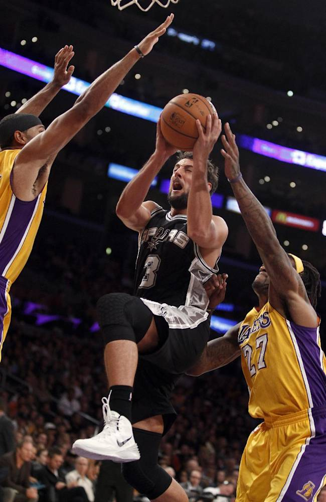 San Antonio Spurs guard Marco Belinelli, center, of Italy, splits the defense of Los Angeles Lakers guard Xavier Henry, left, and Lakers center Jordan Hill, right, in the second half during an NBA basketball game on Friday, Nov. 1, 2013, in Los Angeles. The Spurs won 91-85