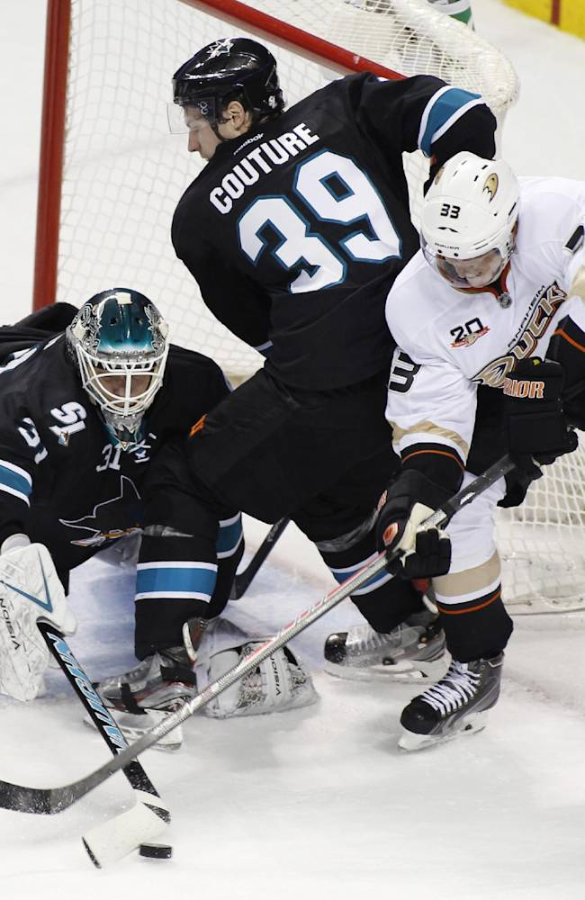 San Jose Sharks goalie Antti Niemi, left, blocks the puck against the Anaheim Ducks during the second period of an NHL hockey game, Sunday, Dec. 29, 2013 in San Jose, Calif. In the center is Sharks' Logan Couture and at left is Ducks' Jekob Silfverburg
