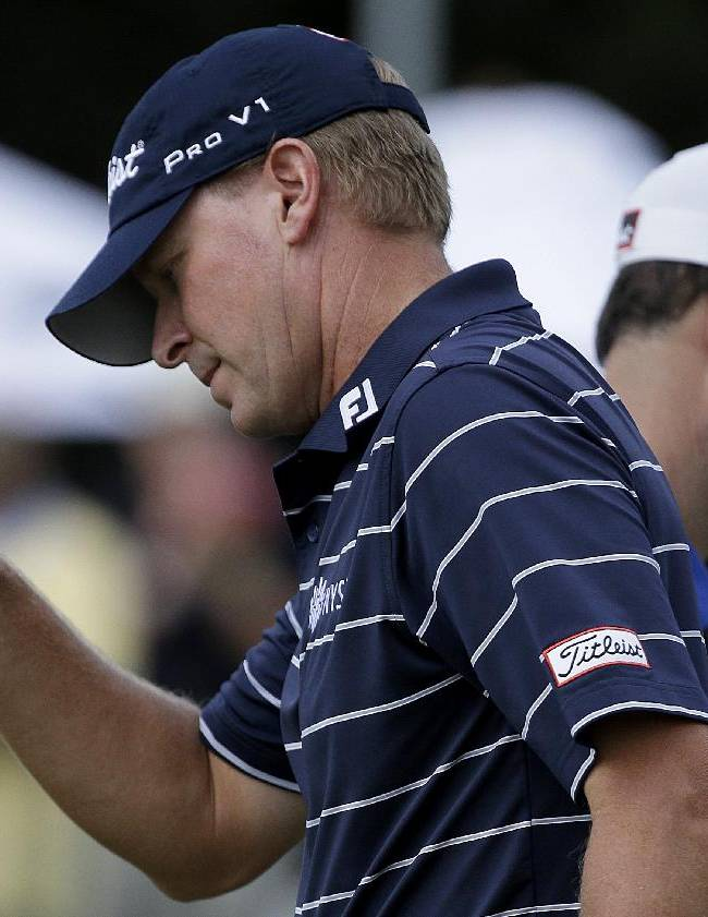 Steve Stricker, left, acknowledges applause from the gallery after sinking a putt on the 10th hole as he passes his pairing partner Zach Johnson, right, during the final round of play in the Tour Championship golf tournament at East Lake Golf Club, in Atlanta, Sunday, Sept. 22, 2013