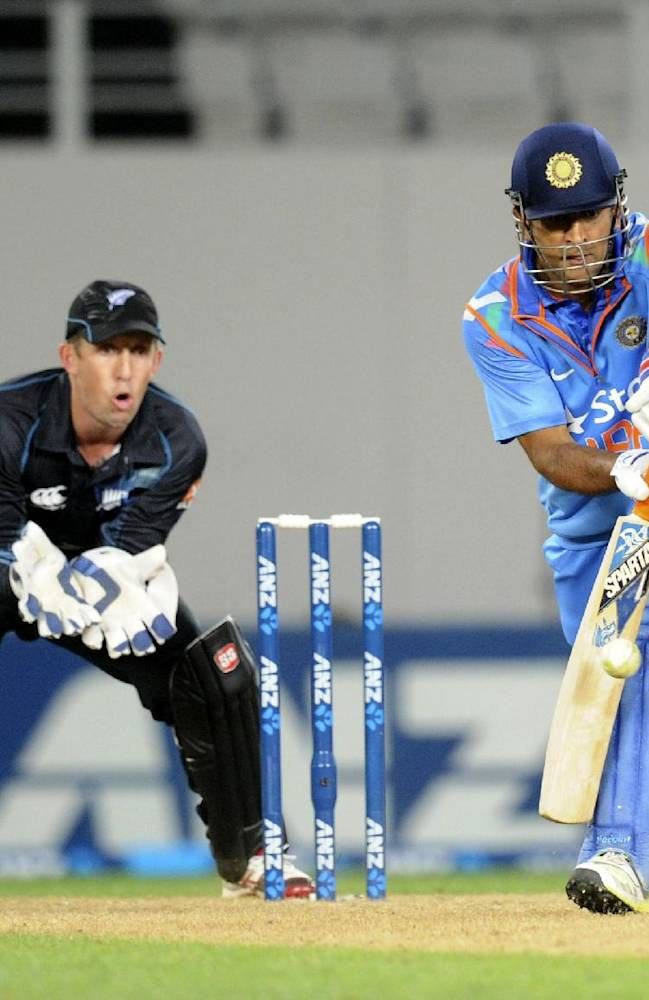 India's MS Dhoni bats in front of New Zealand's Luke Ronchi in their third one day international cricket match at Eden Park in Auckland, New Zealand, Saturday, Jan. 25, 2014