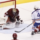 Edmonton Oilers' Taylor Hall (4) scores a goal against Arizona Coyotes' Mike Smith (41) during the third period of an NHL hockey game Wednesday, Oct. 15, 2014, in Glendale, Ariz. The Coyotes defeated the Oilers 7-4 The Associated Press