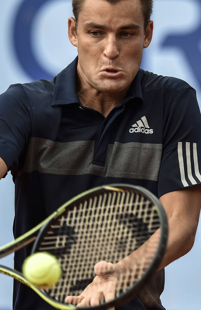 Mikhail Youzhny of Russia  returns a ball  to Kenny De Schepper of France during the second round match at the Suisse Open tennis tournament in Gstaad, Switzerland, Thursday, July 24, 2014
