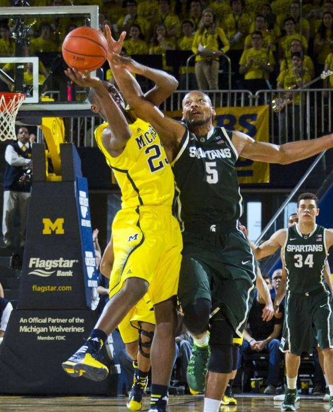 Michigan State center Adreian Payne (5) knocks the ball out Michigan guard Caris LeVert's (23) hands in the second half of an NCAA college basketball game at Crisler Center in Ann Arbor, Mich., Sunday, Feb. 23, 2014. Michigan won 79-70