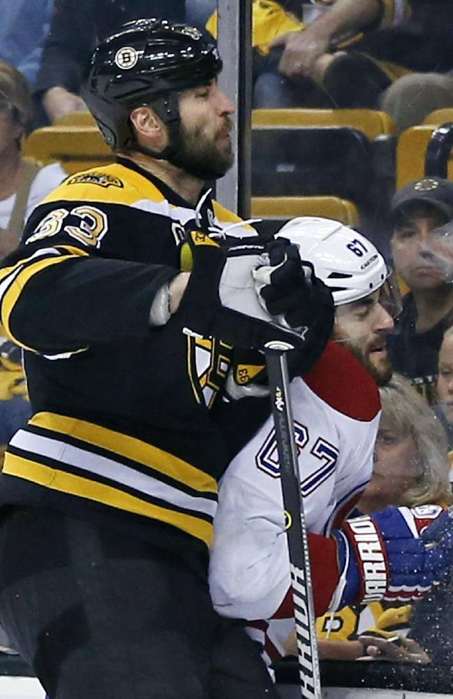 Boston Bruins defenseman Zdeno Chara (33) checks Montreal Canadiens left wing Max Pacioretty (67) into the boards during the first period in Game 7 of an NHL hockey second-round playoff series in Boston, Wednesday, May 14, 2014