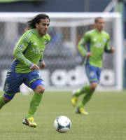 Seattle Sounders' Mauro Rosales, left, dribbles the ball in the second half of an MLS soccer match against the New England Revolution, Saturday, April 13, 2013, in Seattle. (AP Photo/Ted S. Warren)