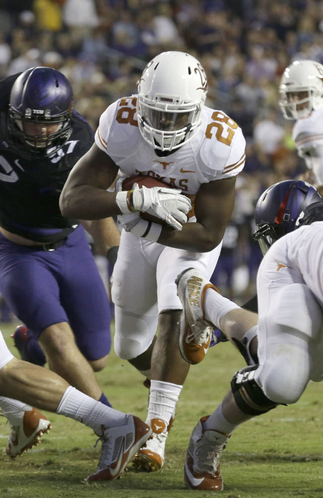 Texas running back Malcolm Brown (28) finds a hole and runs in to score a touchdown during the first half of an NCAA college football game against TCU, Saturday, Oct. 26, 2013, in Fort Worth, Texas.  Texas' Geoff Swaim (82) and Mason Walters (72) and TCU's Jon Koontz (97) are in on the play