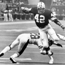 FILE - In this Sept. 30, 1979, file photo, New Orleans Saints running back Chuck Muncie (42) breaks a tackle by New York Giants safety Beasley Reece and heads for the end zone to score a touchdown during an NFL football game at the Superdome in New Orleans. The Saints announced Tuesday, May 14, 2013, that  Muncie, a Pro Bowl running back with both the Saints and San Diego Chargers, has died. He was 60.  (AP Photo/File