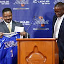 Tulsa's new men's basketball coach Frank Haith holds a uniform as he stands near the podium with athletic director Derrick Gragg at a news conference Friday, April 18, 2014, in Tulsa, Okla The Associated Press