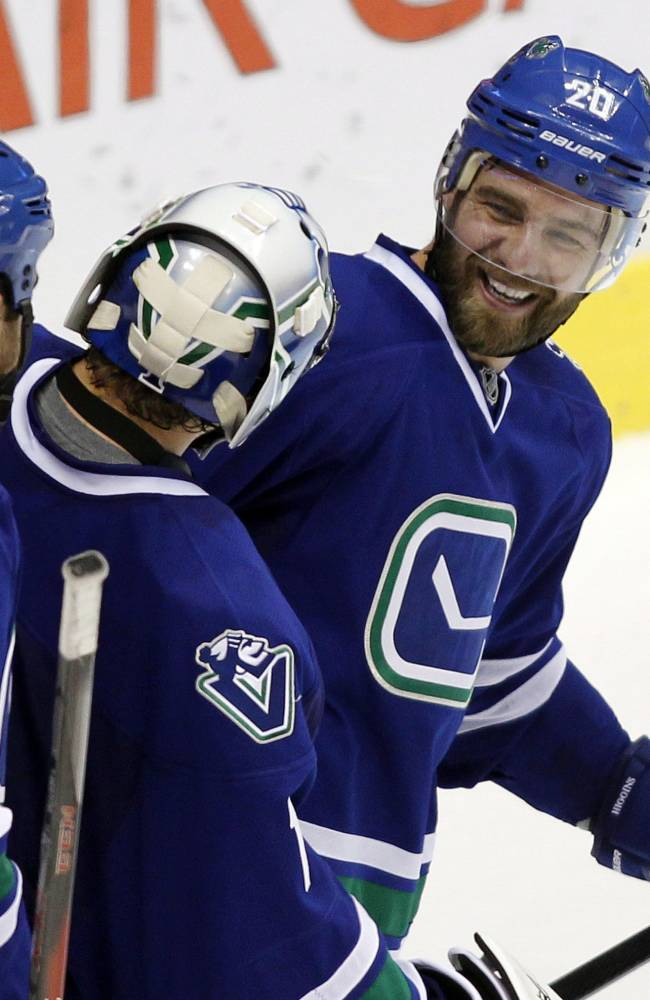 Vancouver Canucks' Chris Higgins (20) celebrates his game winning goal against the Phoenix Coyotes with teammates Roberto Luongo and Tom Sestito during overtime NHL hockey action in Vancouver,  British Columbia, on Friday Dec. 6, 2013