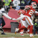 Kansas City Chiefs running back Jamaal Charles (25) scores a touchdown as Seattle Seahawks cornerback Byron Maxwell (41) pulls on his jersey in the first half of an NFL football game in Kansas City, Mo., Sunday, Nov. 16, 2014 The Associated Press