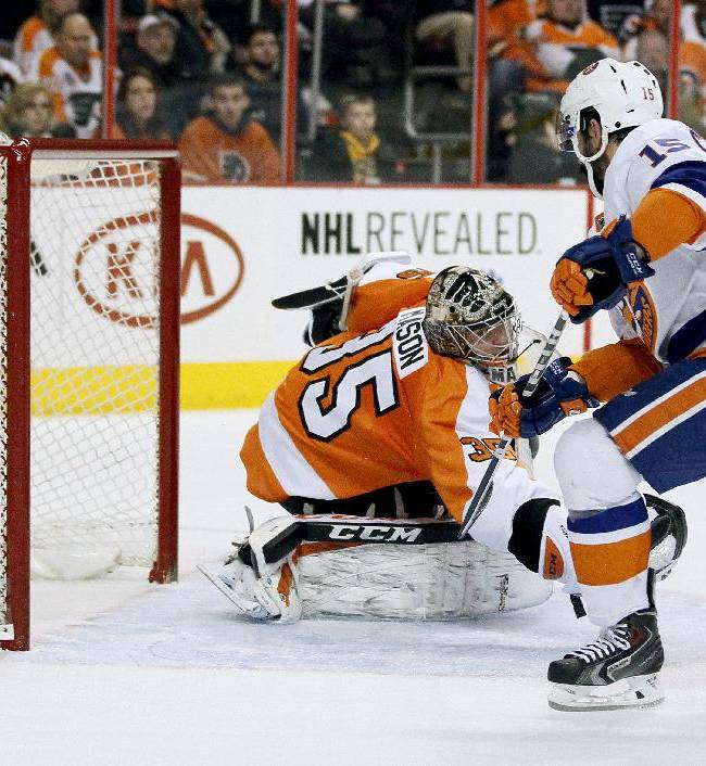 New York Islanders' Cal Clutterbuck, right, puts the puck in the back of the net past Philadelphia Flyers goalie Steve Mason during the first period of an NHL hockey game, Saturday, Jan. 18,  2014, in Philadelphia