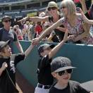 Children, coaches and parents walk the warning track on Little League day at Angel Stadium before a baseball game between the Chicago White Sox and the Los Angeles Angels in Anaheim, Calif., Sunday, May 19, 2013. (AP Photo/Reed Saxon)