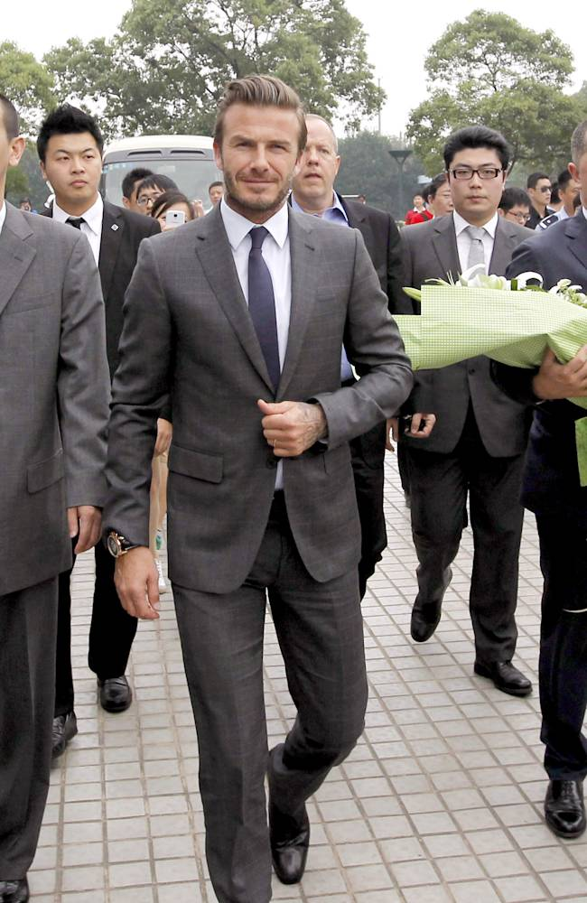 In this photo provided by China's Xinhua News Agency, David Beckham arrives in Shanghai, east China, Wednesday, June 19, 2013.   Beckham is on a seven-day visit to China, and will attend a Chinese Super League soccer match, as part of his role as ambassador to China's top league