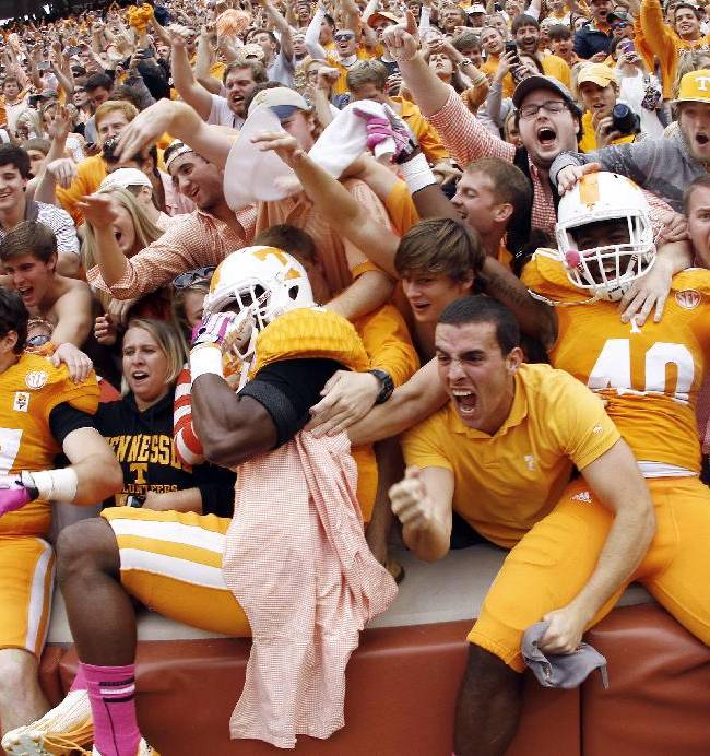 Tennessee linebacker Raiques Crump (40), defensive back Michael F. Williams, center, and linebacker John Propst (47) celebrate with fans after their 23-21 victory over South Carolina in an NCAA college football game on Saturday, Oct. 19, 2013 in Knoxville, Tenn