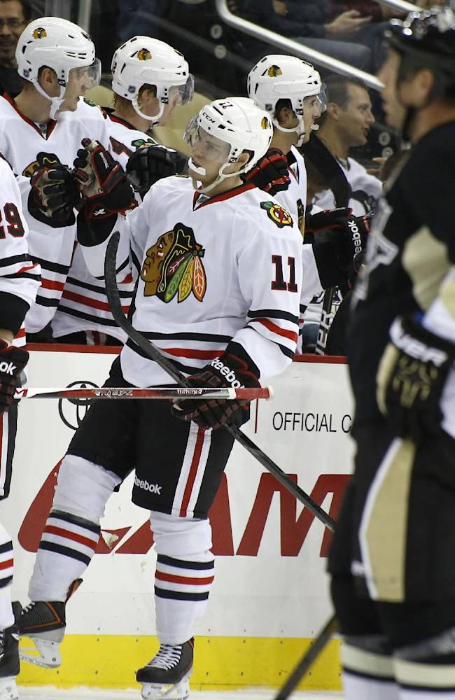 Chicago Blackhawks' Jeremy Morin (11) skates past Pittsburgh Penguins' Rob Scuderi (4) as he is greeted by teammates on the bench after scoring in the second period of an NHL preseason hockey game on Monday, Sept. 23, 2013, in Pittsburgh