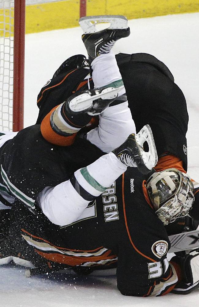Dallas Stars' Alex Goligoski, top left, and Anaheim Ducks' Ben Lovejoy stumble over Anaheim Ducks goalie Frederik Andersen, of Denmark, in the first period of Game 5 of the first-round NHL hockey Stanley Cup playoff series on Friday, April 25, 2014, in Anaheim, Calif