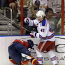 Florida Panthers' Colby Robak (47) slams into the wall as he tries to steal the puck from New York Rangers' Arron Asham (45)