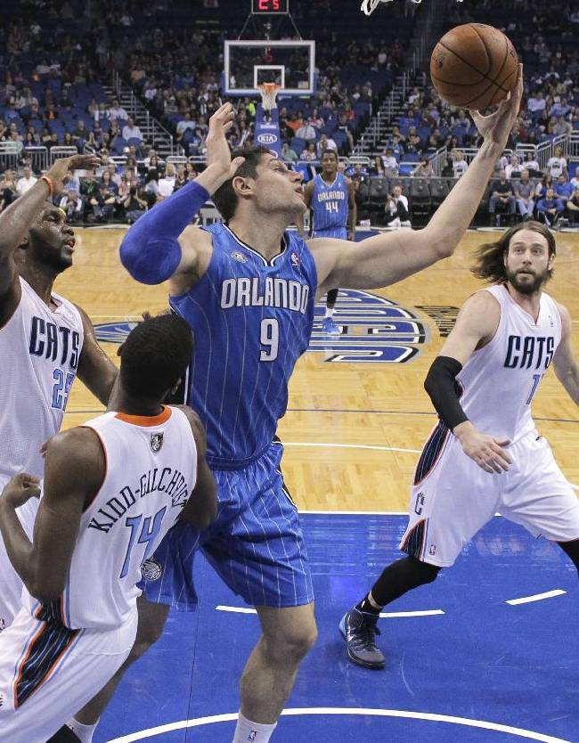 Orlando Magic's Nikola Vucevic (9) grabs an offensive rebound in front of Charlotte Bobcats' Al Jefferson, left, Michael Kidd-Gilchrist (14) and Josh McRoberts, right, during the first half of an NBA basketball game in Orlando, Fla., Friday, March 28, 2014