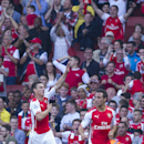 Arsenal's Laurent Koscielny, left, celebrates with teammate Santi Cazorla after scoring against Crystal Palace, during their English Premier League soccer match, at Emirates Stadium, in London, Saturday, Aug. 16, 2014