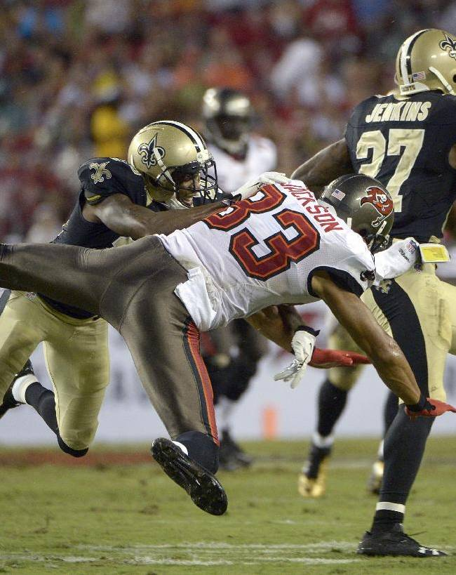 Tampa Bay Buccaneers wide receiver Vincent Jackson (83) is sent flying by New Orleans Saints cornerback Keenan Lewis (28) after Saints' free safety Malcolm Jenkins (27) intercepted a pass by Buccaneers' Josh Freeman during the third quarter of an NFL football game on Sunday, Sept. 15, 2013, in Tampa, Fla