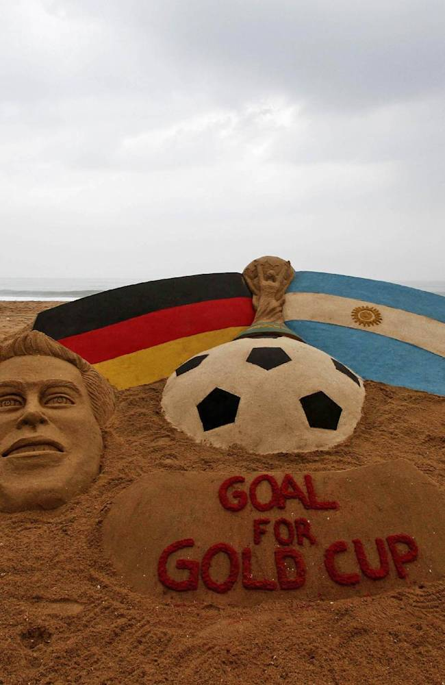 A candy floss vendor walks past a sand sculpture depicting the Argentinian and German flags and soccer players created on the eve of the soccer World Cup final, in Puri, India, Saturday, July 12, 2014. Argentina will face Germany in the final of the 2014 soccer World Cup on Sunday