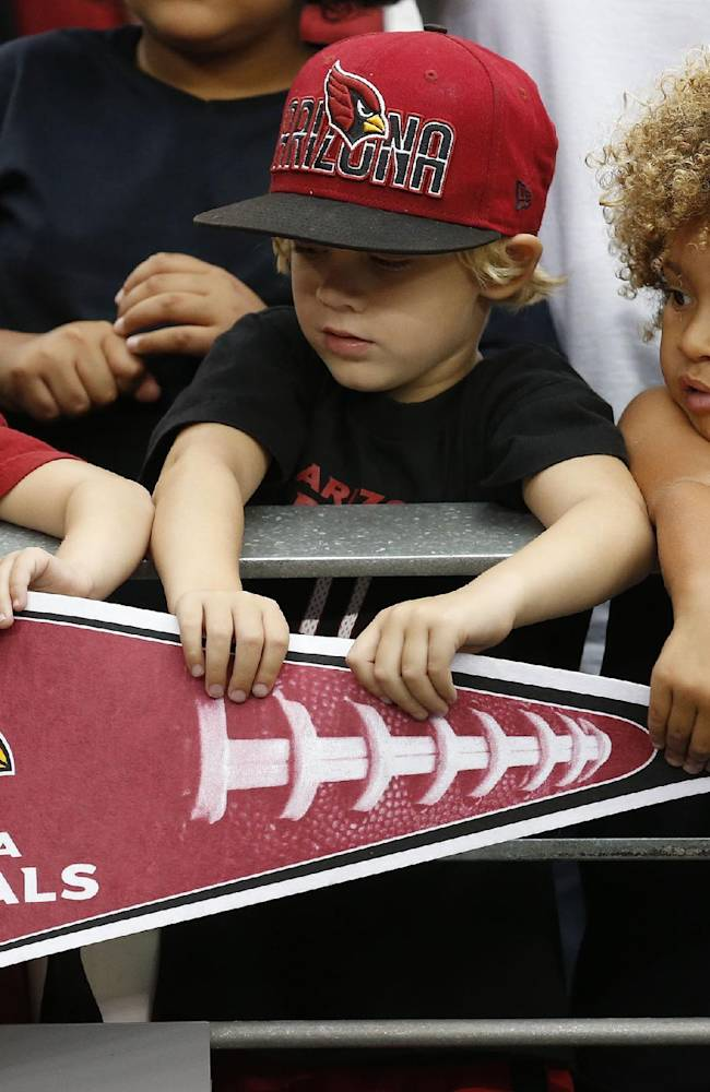 Three young Arizona Cardinals fans check out an autograph on a pennant from player Dan Williams after the first day of the NFL football team's training camp Saturday, July 26, 2014, in Glendale, Ariz