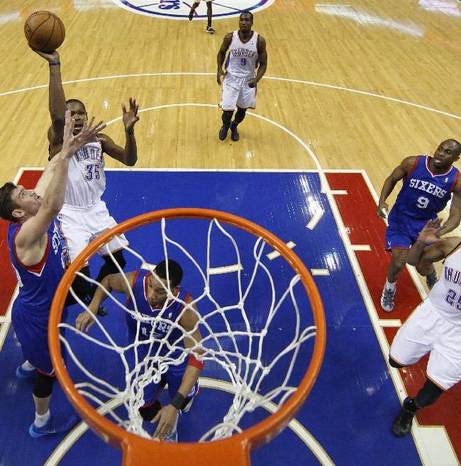 Oklahoma City Thunder's Kevin Durant puts up a shot with Philadelphia 76ers' Spencer Hawes, left, defending during the first half of an NBA basketball game, Saturday, Jan. 25, 2014, in Philadelphia