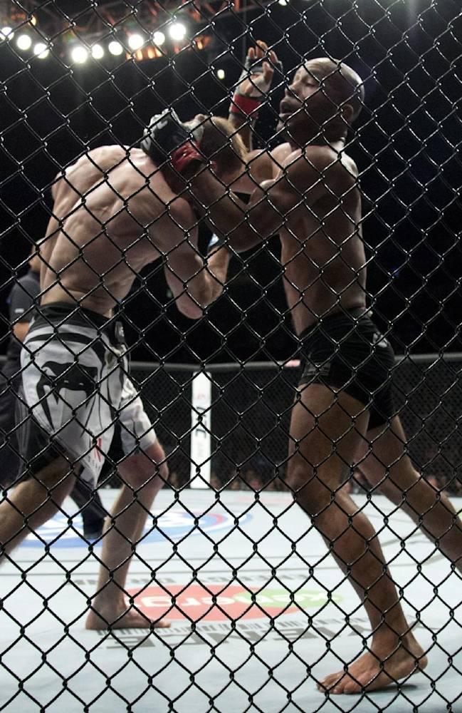 Demetrious Johnson, of the United States, right, fights Ali Bagautinov, of Russia, during the flyweight bout at UFC 174 in Vancouver, British Columbia, Saturday, June, 14, 2014