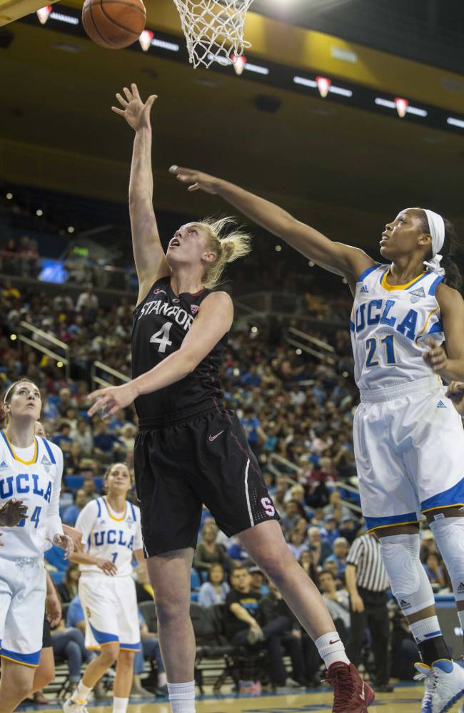 Stanford forward Taylor Greenfield, left,  goes up for a lay-up against UCLA guard Nirra Fields, right, in the first half of an NCAA college basketball game, Sunday, Feb. 23, 2014 in Los Angeles