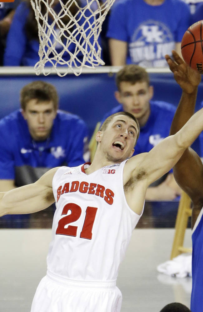 Wisconsin guard Josh Gasser (21) and Kentucky center Dakari Johnson (44) go after a rebound during the first half of the NCAA Final Four tournament college basketball semifinal game Saturday, April 5, 2014, in Arlington, Texas