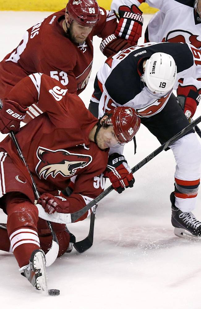 Phoenix Coyotes' Antoine Vermette (50) kicks the puck away from New Jersey Devils' Travis Zajac (19) as Coyotes' Derek Morris (53) skates into the action during the third period of an NHL hockey game, Saturday, Jan. 18, 2014, in Glendale, Ariz.  The Coyotes won 3-2