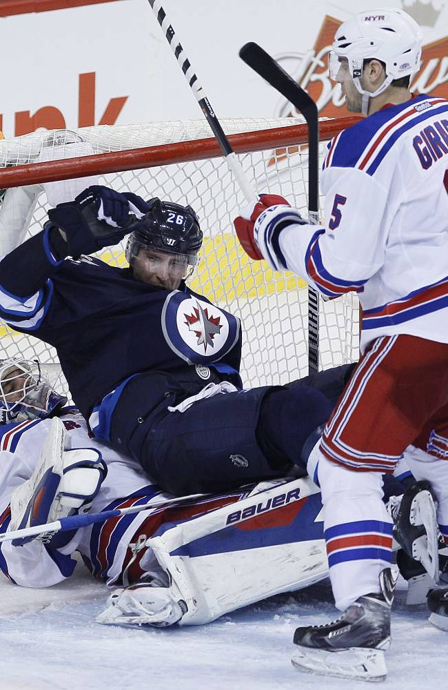 Winnipeg Jets' Blake Wheeler (26) gets checked into New York Rangers goaltender Henrik Lundqvist (30) by Dan Girardi (5) during third period NHL action in Winnipeg on Friday, March 14, 2014