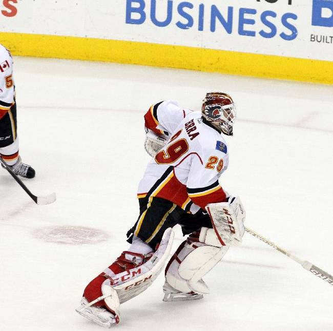 Calgary Flames goalie Reto Barra heads for the bench past captain Mark Giordano with a minute remaining in the third period of an NHL hockey game, Saturday, Feb. 8, 2014, in Philadelphia. The Flyers won 2-1