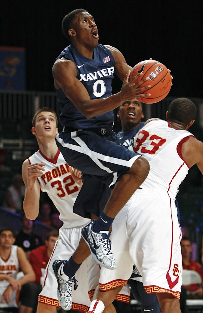 Xavier's Semaj Christon, center, drives to the basket against Southern California's D.J. Haley, right, and Nikola Jovanovic during the first half of an NCAA college basketball game in Paradise Island, Bahamas, Saturday, Nov. 30, 2013. USC won 84-78