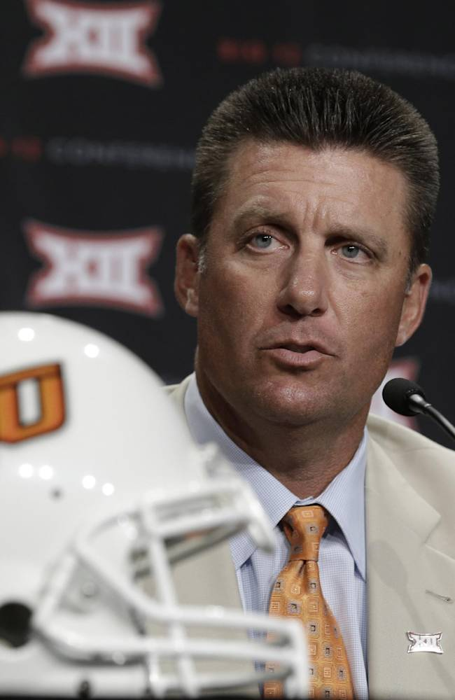 Oklahoma State head coach Mike Gundy speaks to reporters during the NCAA college Big 12 Conference football media days in Dallas, Monday, July 21, 2014