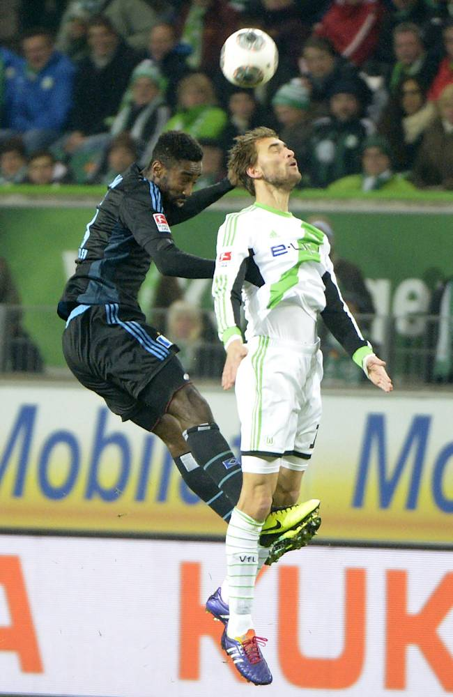 In this picture taken Friday Nov. 29, 2013, Wolfsburg's  Bas Dost, right, and Hamburg's Johan Djourou, challenge for the ball  during the German Bundesliga soccer match between VfL Wolfsburg and Hamburger SV, in Wolfsburg, Germany