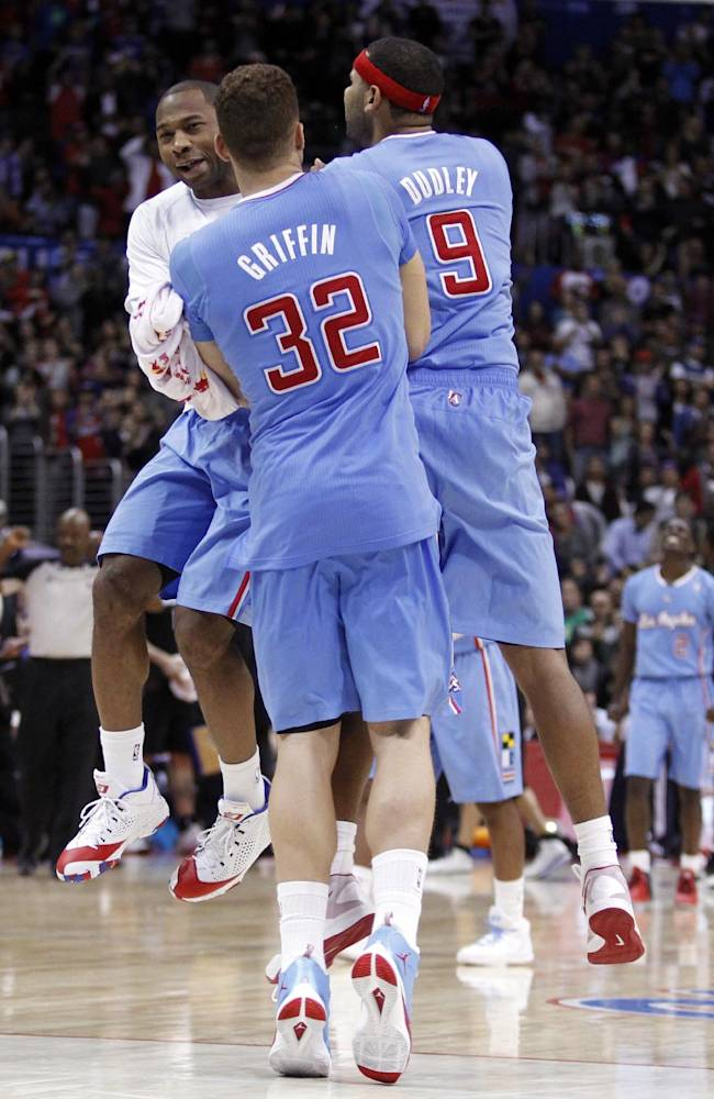 Los Angeles Clippers guard Willie Green, left, forward Blake Griffin (32) and forward Jared Dudley (9) celebrate after taking the lead against the Minnesota Timberwolves in the overtime period of an NBA basketball game in Los Angeles on Sunday, Dec. 22, 2013. Clippers won the game 120-116 in overtime