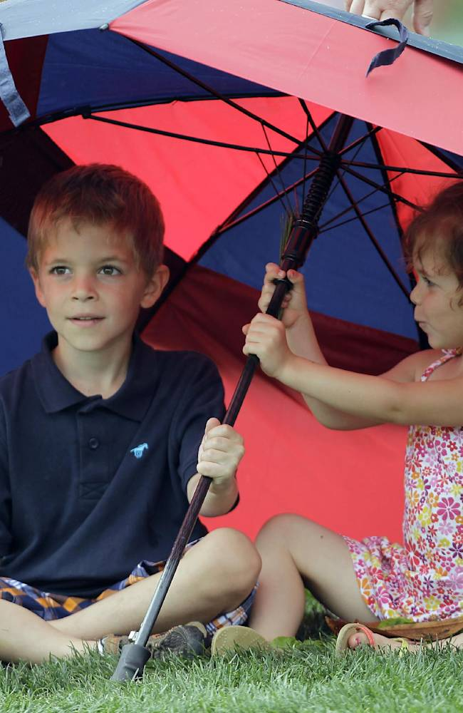 Owen Uher, 5, and sister, Molly, 4, both from Charlotte, protect themselves from the light rain, but stronger winds, at the 16th green during the pro-am of the Wells Fargo Championship golf tournament at Quail Hollow Club in Charlotte, N.C., Wednesday, April 30, 2014
