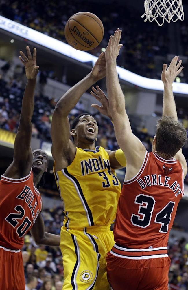 Indiana Pacers forward Danny Granger, center, is fouled as he shoots between Chicago Bulls forward Tony Snell, left, and shooting guard Mike Dunleavy in the second half of an NBA preseason basketball game in Indianapolis, Saturday, Oct. 5, 2013. The Bulls won 82-76