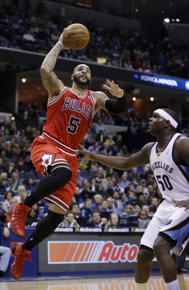 Chicago Bulls' Carlos Boozer (5) goes to the basket over Memphis Grizzlies' Zach Randolph (50) in the first half of an NBA basketball game in Memphis, Tenn., Monday, Dec. 30, 2013