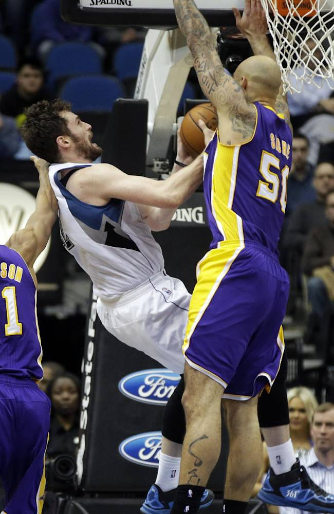 Minnesota Timberwolves' Kevin Love, center, is fouled by Los Angeles Lakers' Robert Sacre, right, during the second half of an NBA basketball game, Tuesday, Feb. 4, 2014, in Minneapolis. The Timberwolves won 109-99. Love, who led his team with 31 points and 17 rebounds, fell to the floor and was attended to but continued in the game