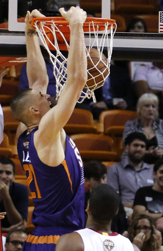 Phoenix Suns center Alex Len (21) dunks between Miami Heat guard Dwyane Wade (3) and forward Luol Deng (9) during the first quarter of an NBA basketball game, Monday, March 2, 2015, in Miami. (AP Photo/Joe Skipper)