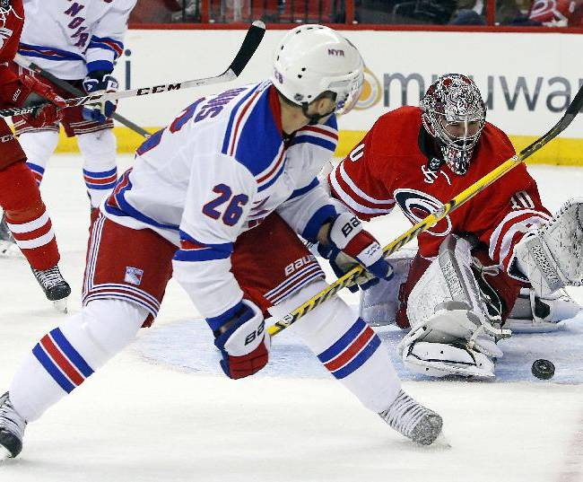 New York Rangers' Martin St. Louis (26) has his shot blocked by Carolina Hurricanes goalie Cam Ward (30) during the first period of an NHL hockey game in Raleigh, N.C., Tuesday, March 11, 2014