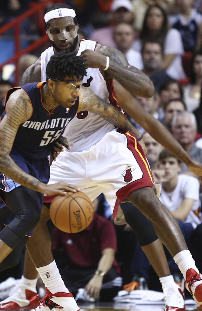 Miami Heat's LeBron James (6) blocks Charlotte Bobcats' Chris Douglas-Robert (55) during the second half of an NBA basketball game in Miami, Monday, March 3, 2014. LeBron James scored a team record of 61 points. The Heat won 124-107