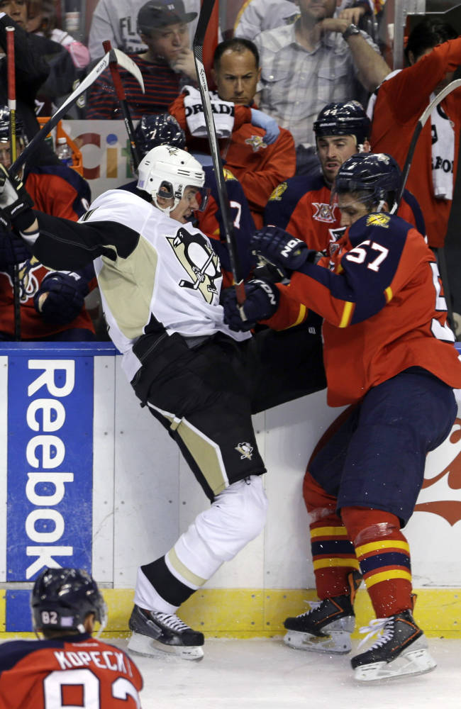 Pittsburgh Penguins' Evgeni Malkin, left, is checked by Florida Panthers' Marcel Goc (57) in the first period of an NHL hockey game on Friday, Oct. 11, 2013, in Sunrise, Fla. The Panthers won 6-3