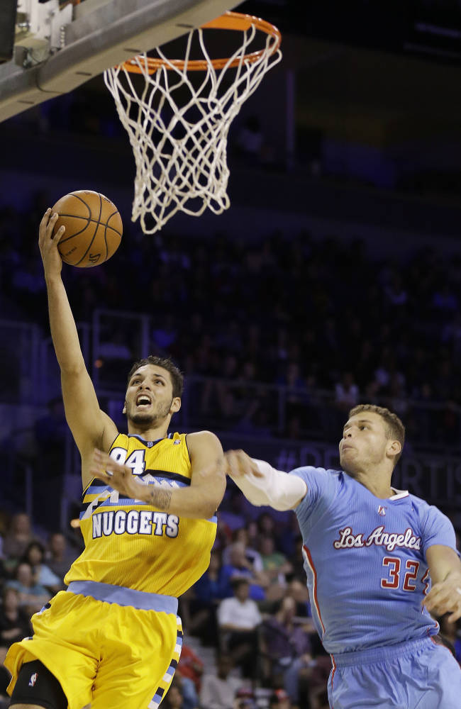 The Los Angeles Clippers' Blake Griffin covers a shot from the Denver Nuggets' Evan Fournier during the second half of a preseason NBA basketball game on Saturday, Oct. 19, 2013, in Las Vegas. The Clippers defeated the Nuggets in overtime 118-111