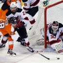 New Jersey Devils' Marek Zidlicky, rear, pushes on Philadelphia Flyers' Claude Giroux (8) trying to make a wrap-around shot as goalie Martin Brodeur defend the crease during the third period in Game 2 of an NHL hockey Stanley Cup second-round playoff series, Tuesday, May 1, 2012, in Philadelphia. The Devils won 4-1 evening the best of seven series at 1-1.(AP Photo/Tom Mihalek)